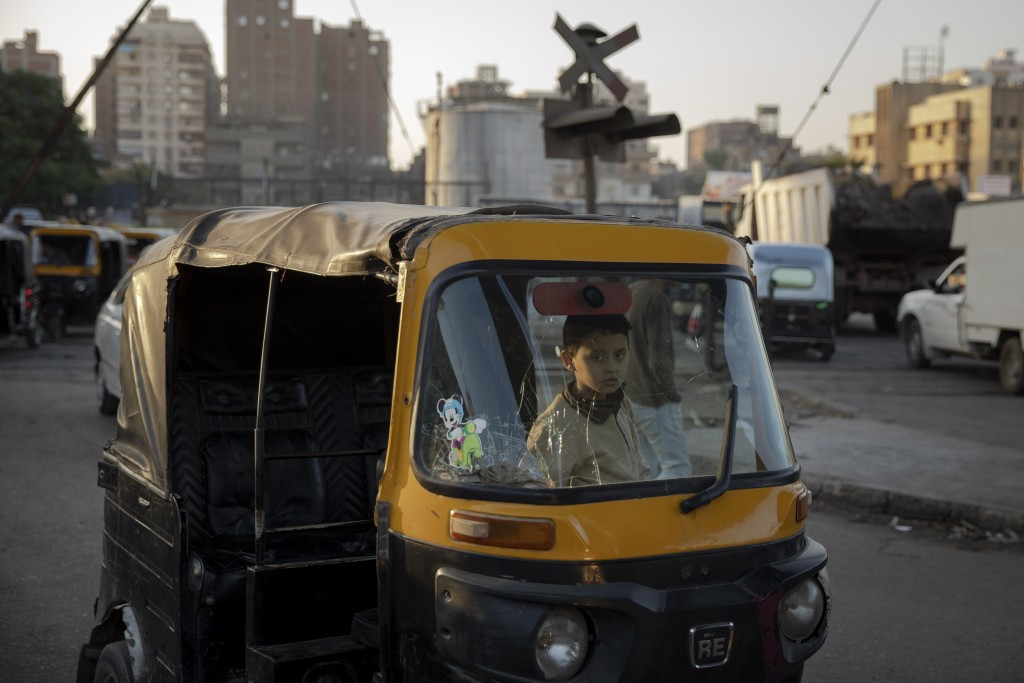 In this Nov. 19, 2019 photo, a boy sits in the driver's seat of a tuk-tuk at a slum in Cairo, Egypt. Motorized rickshaws known as tuk-tuks have ruled ...