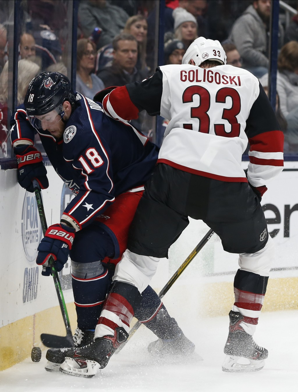Columbus Blue Jackets' Pierre-Luc Dubois, left, and Arizona Coyotes' Alex Goligoski scrap for the puck during the second period of an NHL hockey game ...