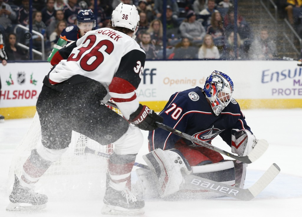 Columbus Blue Jackets' Joonas Korpisalo, right, of Finland, makes a save against Arizona Coyotes' Christian Fischer during the first period of an NHL ...