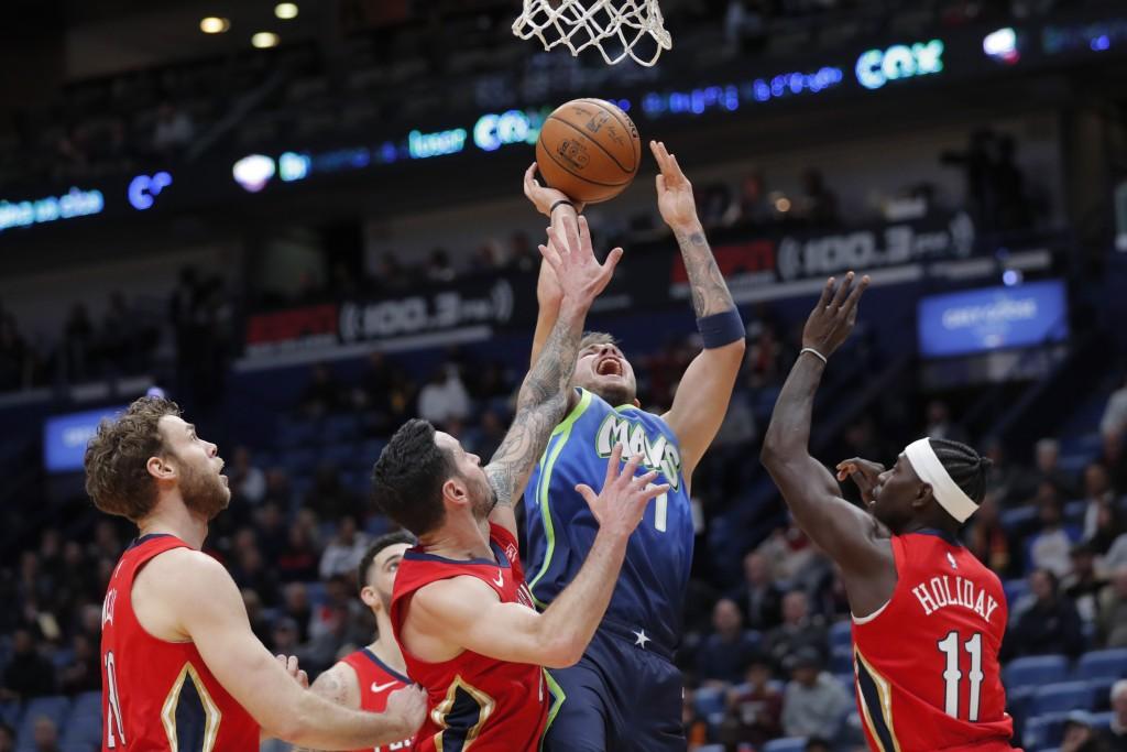 Dallas Mavericks forward Luka Doncic (77) shoots between New Orleans Pelicans forward Nicolo Melli, left, guard JJ Redick and guard Jrue Holiday (11) ...