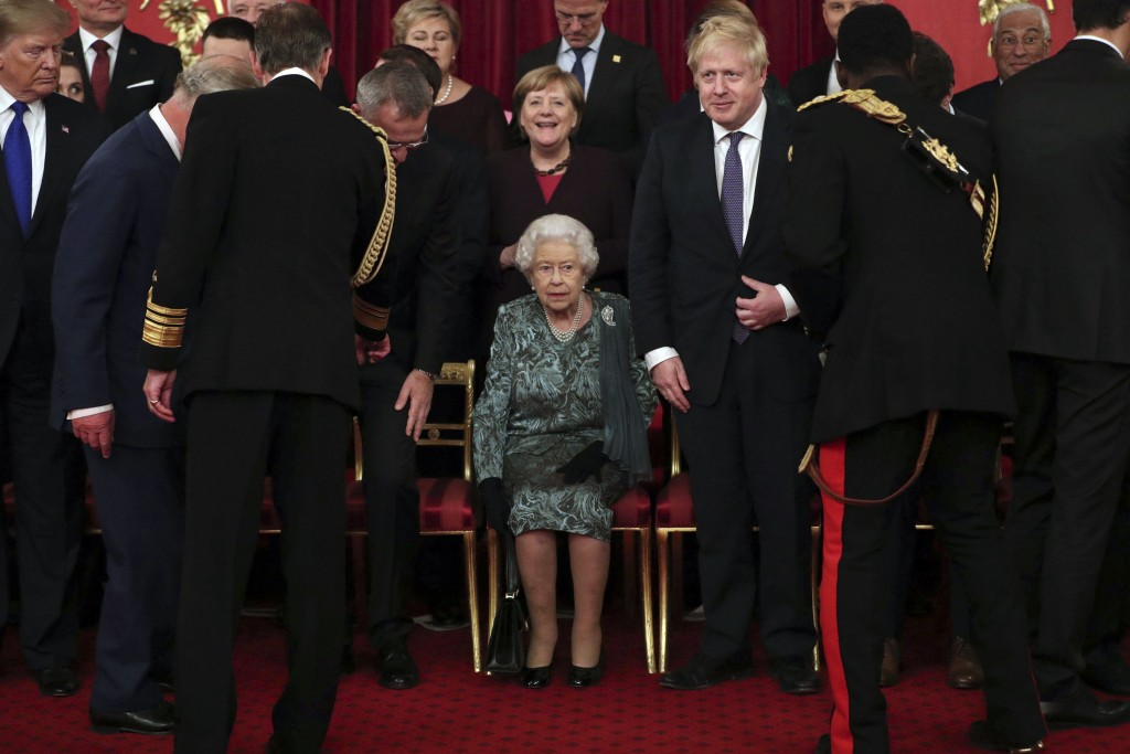 Britain's Queen Elizabeth II, centre, takes her seat with Britain's Prime Minister Boris Johnson and Chancellor of Germany Angela Merkel, behind, befo...