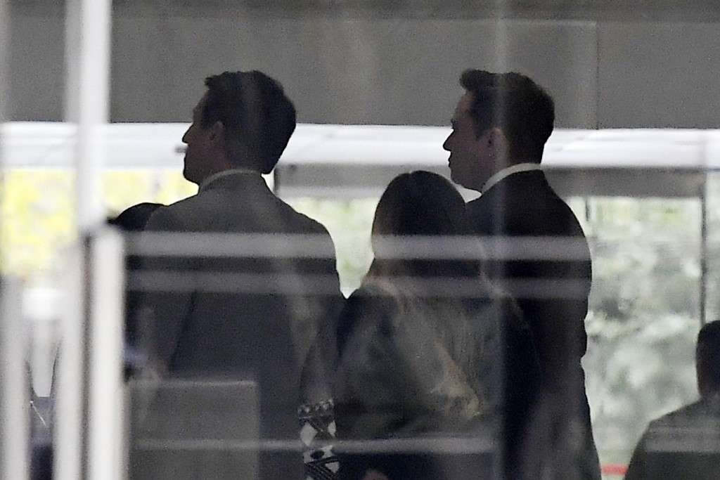 Tesla CEO Elon Musk, right, arrives at federal court, Tuesday, Dec. 3, 2019, in Los Angeles. Musk is going on trial for his troublesome tweets in a ca...