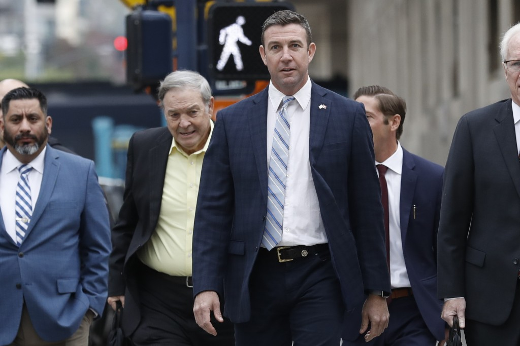 California Republican Rep. Duncan Hunter, center, walks towards federal court in front of his father, former Rep. Duncan L. Hunter, left, Tuesday, Dec...