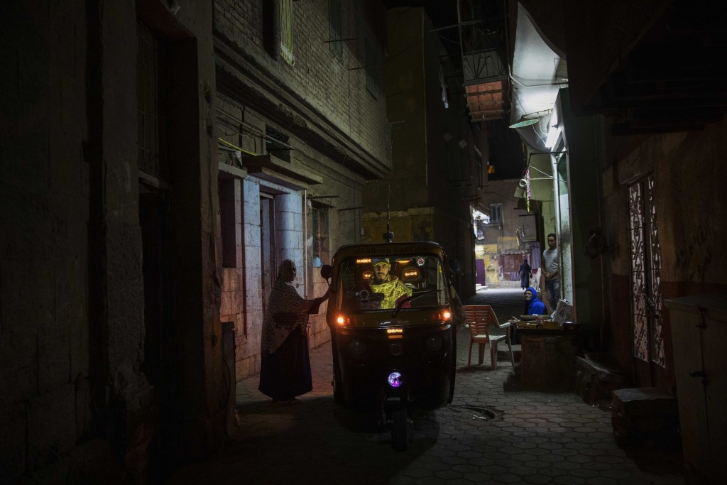 In this Nov. 19, 2019 photo, a woman talks to a tuk-tuk driver in an alleyway of a slum in Cairo, Egypt. Motorized rickshaws known as tuk-tuks have ru...