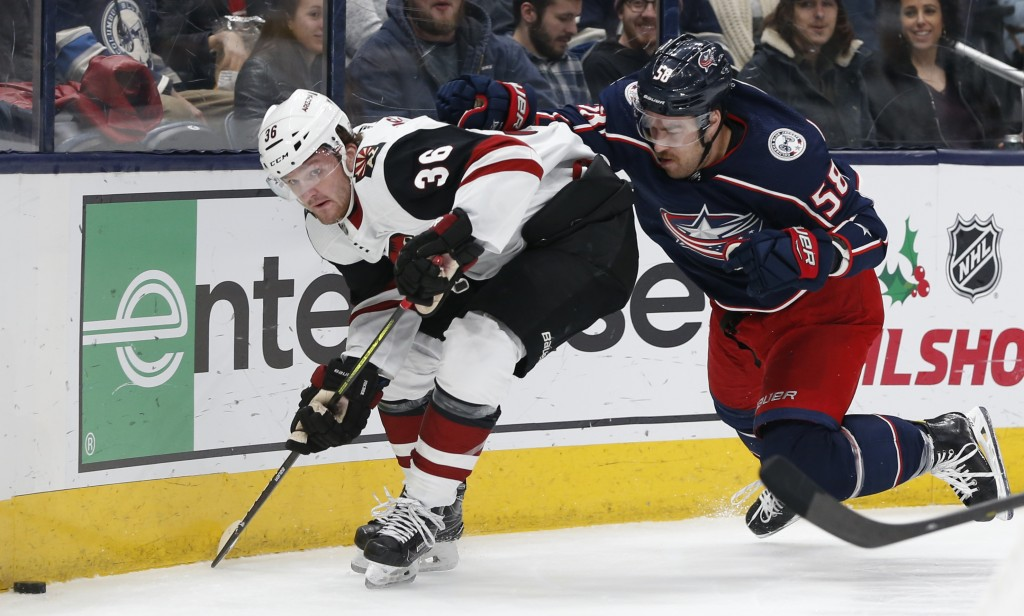 Arizona Coyotes' Christian Fischer, left, skates past Columbus Blue Jackets' David Savard during the first period of an NHL hockey game Tuesday, Dec. ...