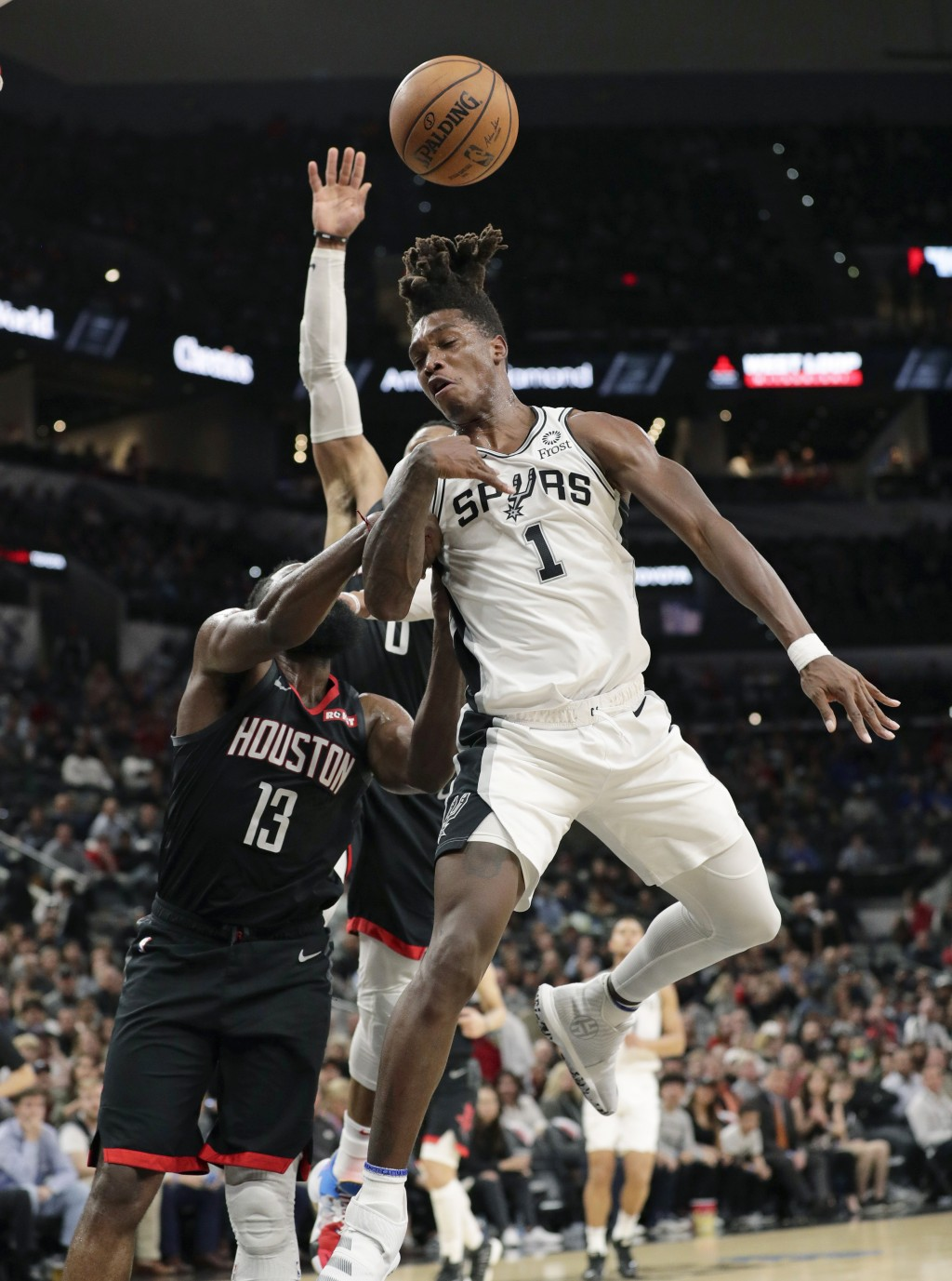 San Antonio Spurs guard Lonnie Walker IV (1) is fouled by Houston Rockets guard James Harden (13) during the second half of an NBA basketball game in ...
