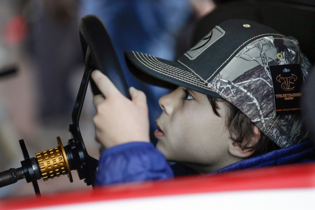 Noah Michel, 8, of Los Angeles, peeks through the steering wheel as he drives a racing simulator Wednesday, Dec. 4, 2019, during NASCAR Champion's Wee...