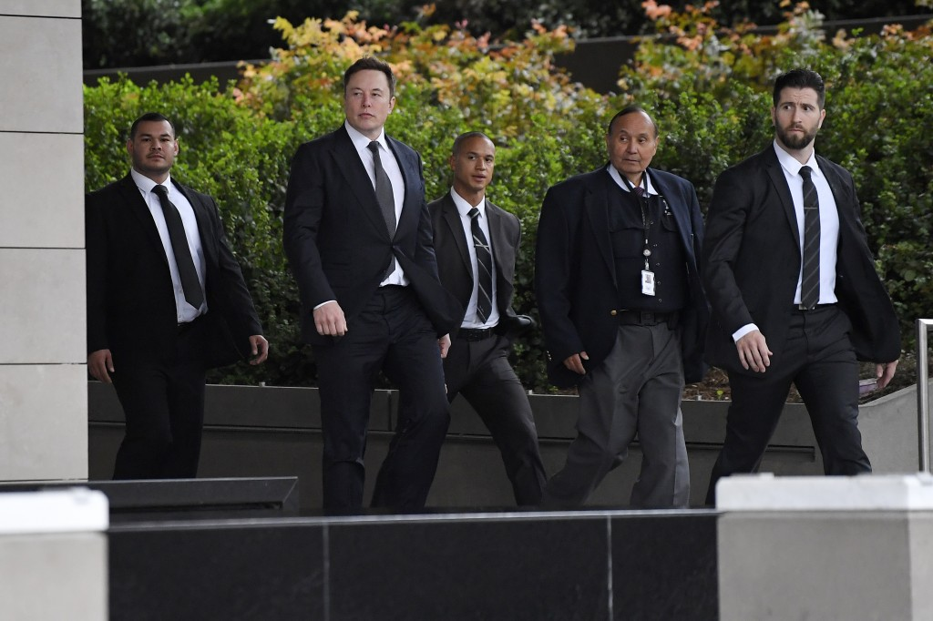 Tesla CEO Elon Musk, second from left, arrives at U.S. District Court Wednesday, Dec. 4, 2019, in Los Angeles. Musk is going on trial for his troubles...