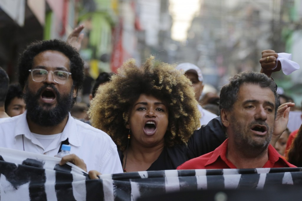 Residents of the Paraisopolis slum take part in a demonstration asking for peace, in Sao Paulo, Brazil, Wednesday, Dec. 4, 2019. Police officers pursu...