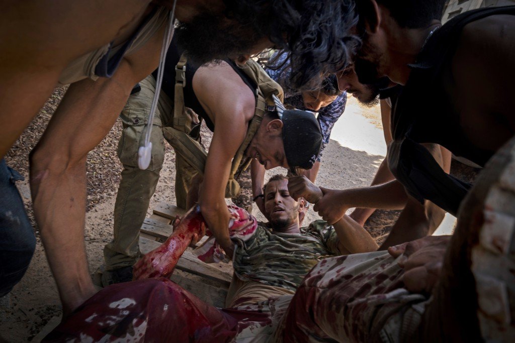 FILE - In this Sept. 7, 2019 file, photo, a mortally wounded fighter of the 'Shelba' unit, allied with the U.N-supported Libyan government, is moved b...