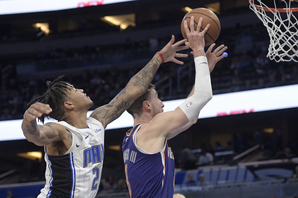 Phoenix Suns forward Frank Kaminsky (8) goes up for a shot in front of Orlando Magic guard Markelle Fultz, left, during the first half of an NBA baske...