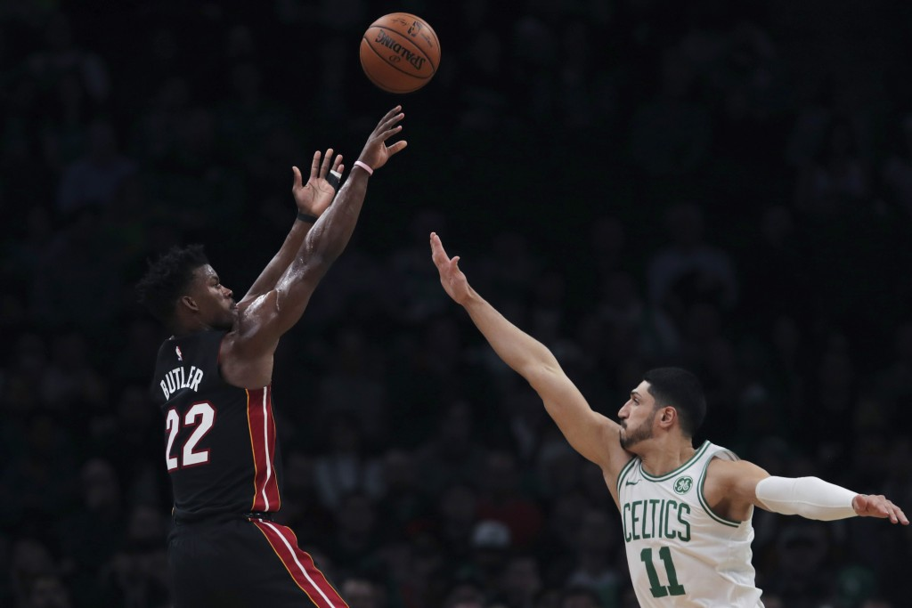 Miami Heat forward Jimmy Butler (22) fires a shot over Boston Celtics center Enes Kanter (11) during the first half of an NBA basketball game in Bosto...