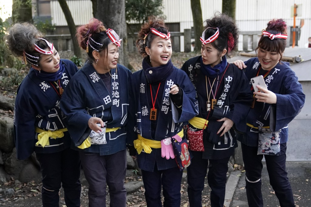 In this Tuesday, Dec. 3, 2019, photo,  participants clad in traditional happi coats prepare for a selfie before the Chichibu Night Festival in Chichib...