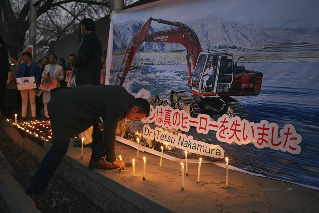 An Afghan man lights a candle in front of a poster showing Tetsu Nakamura , a Japanese physician engaged in aid work who was killed Wednesday, Dec. 4 ...