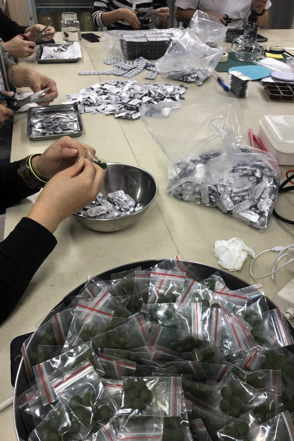 FILE - In this Sunday, Dec. 1, 2019, photo, workers pack multi-colored supplement pills in small resealable bags at an industrial building in Hong Kon...