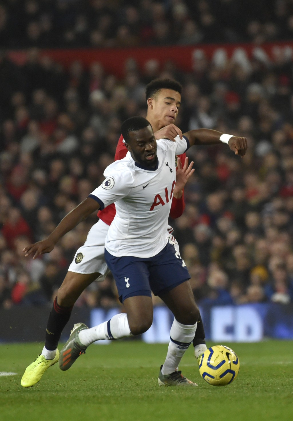Tottenham's Tanguy Ndombele, left, and Manchester United's Mason Greenwood challenge for the ball during the English Premier League soccer match betwe...