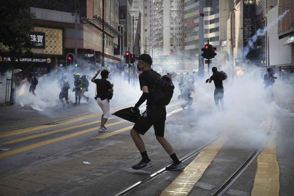 FILE - In this Saturday, Nov. 2, 2019, file photo, pro-democracy protesters react as police fire tear gas during a protest in Hong Kong. By day, the s...