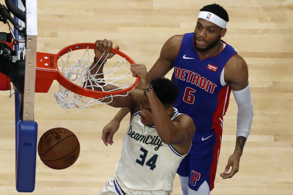 Milwaukee Bucks forward Giannis Antetokounmpo (34) dunks as Detroit Pistons guard Bruce Brown (6) watches during the first half of an NBA basketball g...