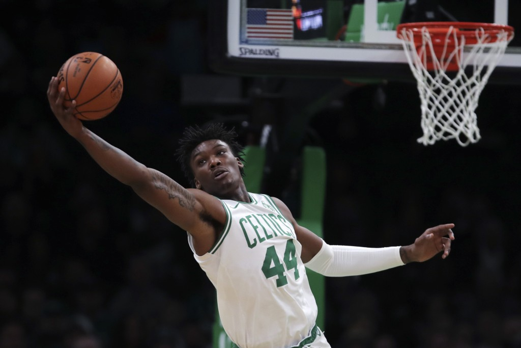 Boston Celtics center Robert Williams III (44) reaches for a rebound during the first half of an NBA basketball game against the Miami Heat in Boston,...