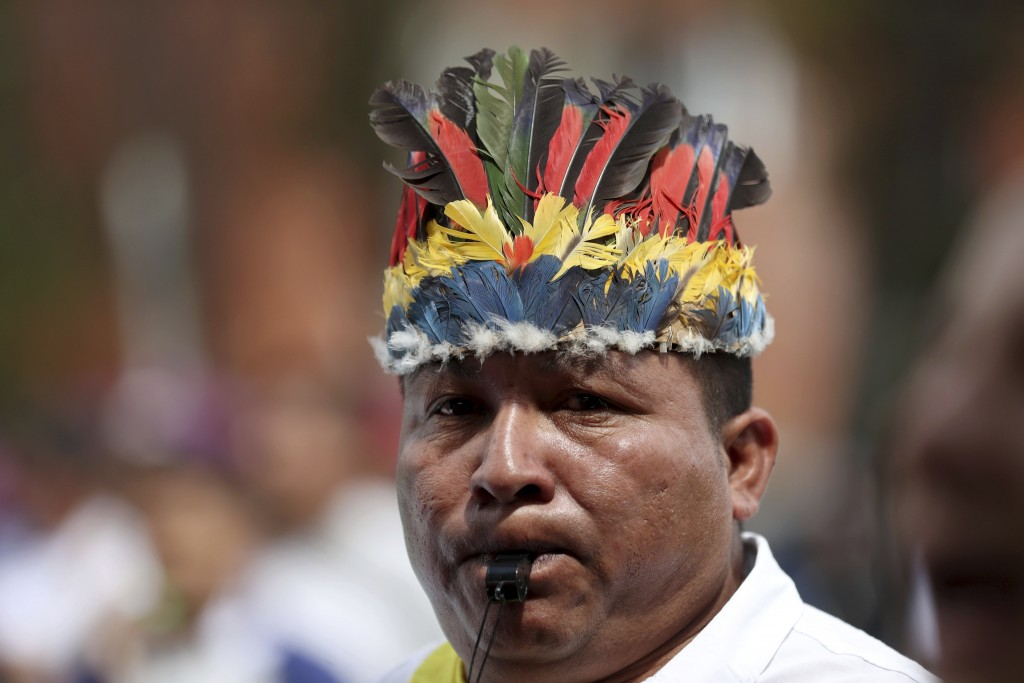 An indigenous man blows on a whistle during a national strike in Bogota, Colombia, Wednesday, Dec. 4, 2019. Colombia's recent wave of demonstrations b...