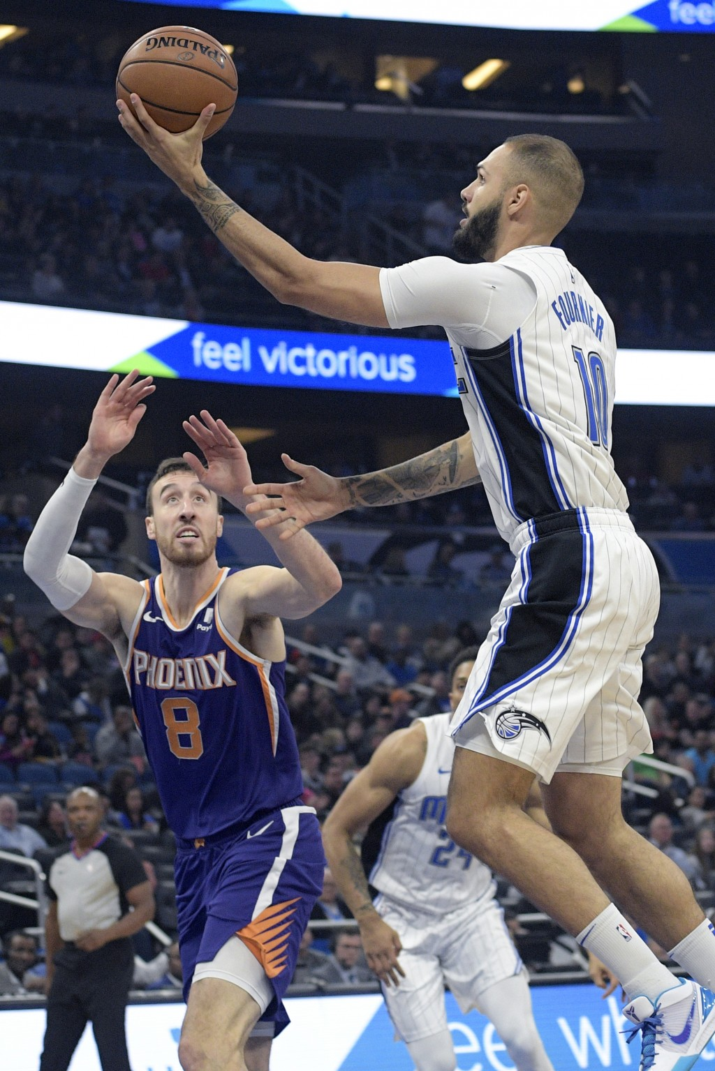 Orlando Magic guard Evan Fournier (10) goes up for a shot in front of Phoenix Suns forward Frank Kaminsky (8) during the first half of an NBA basketba...