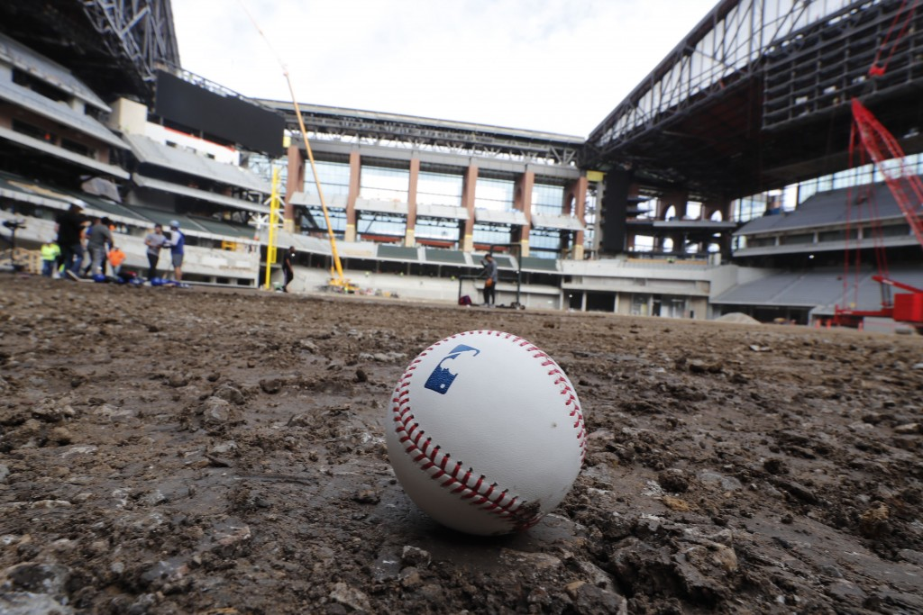 A baseball lies on packed dirt after for a short batting practice during a tour of the under construction baseball field at the new Texas Rangers stad...