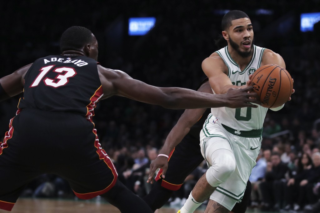 Boston Celtics forward Jayson Tatum (0) drives to the basket against Miami Heat center Bam Adebayo (13) during the first half of an NBA basketball gam...
