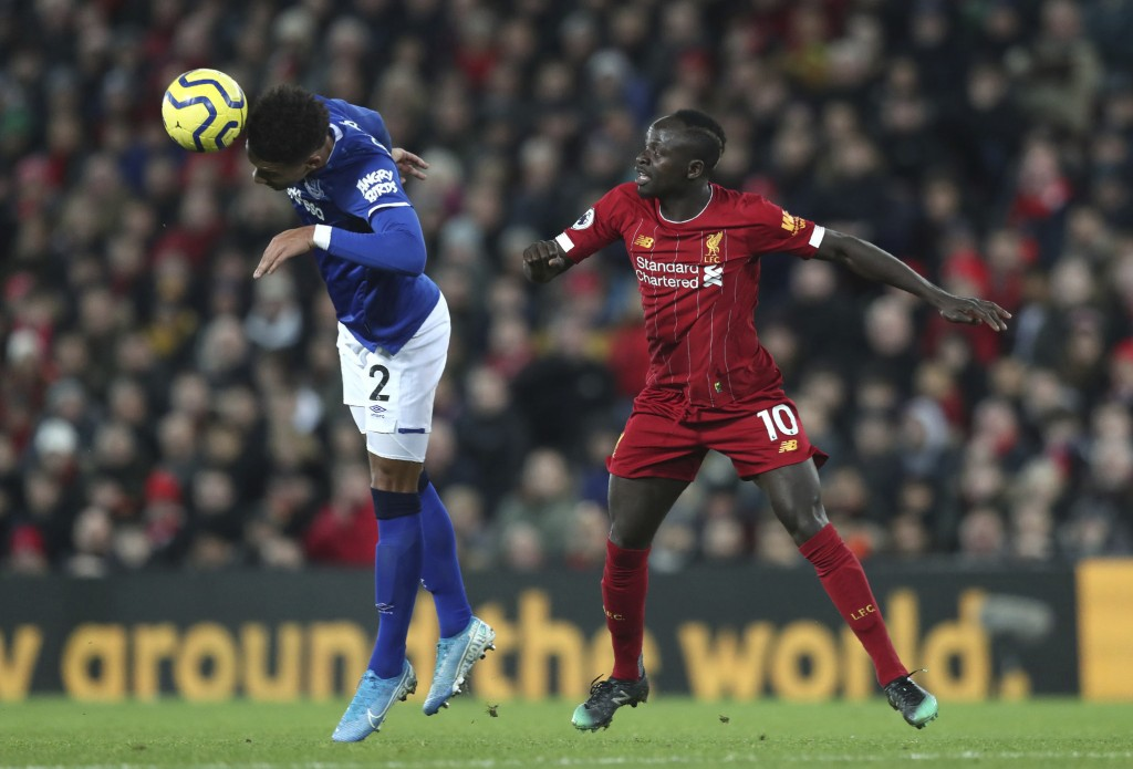 Liverpool's Sadio Mane, right, challenges for the ball with Everton's Mason Holgate during the English Premier League soccer match between Liverpool a...
