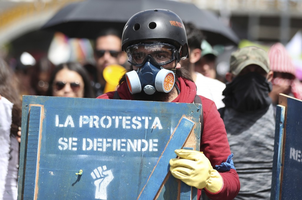 """An anti-government demonstrator carries a shield with text stenciled on it that reads """"Protests are defended"""" during a national strike in Bogota, Colo..."""