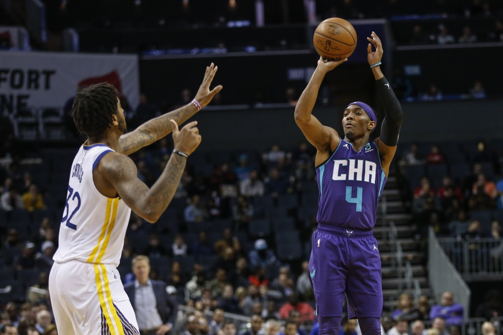 Charlotte Hornets guard Devonte' Graham (4) shoots over Golden State Warriors forward Marquese Chriss during the first half of an NBA basketball game ...