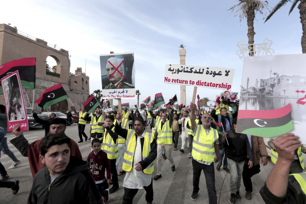 FILE - In this April 19, 2019 file photo, protesters wear yellow vests at a protest as they wave national flags and chant slogans against Libya's Fiel...