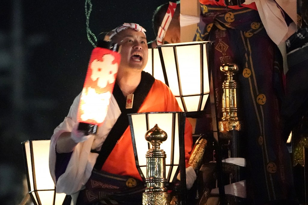In this Tuesday, Dec. 3, 2019, photo,  a man holding a lantern shouts on a lantern-covered float going to the town central square during the Chichibu ...