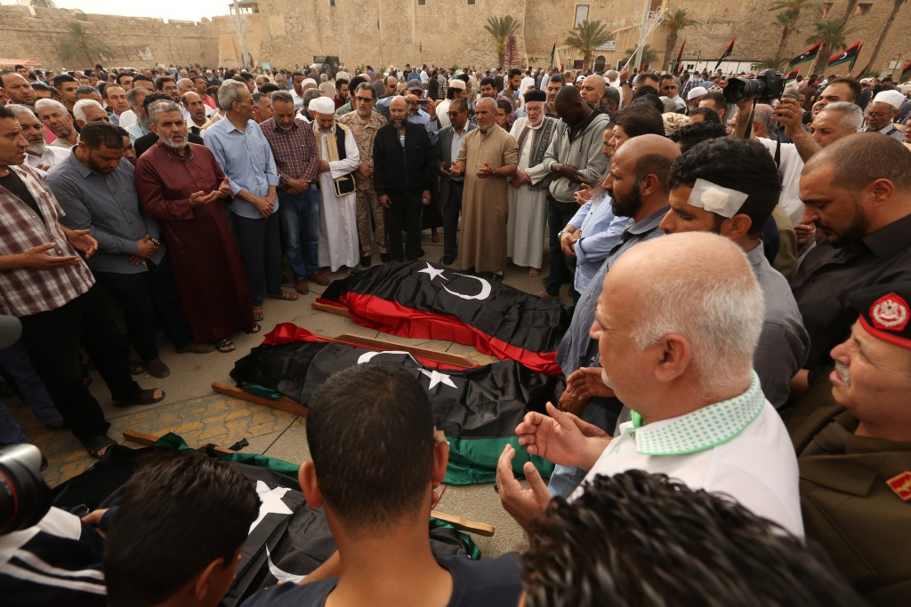 FILE - In this April 24, 2019 file photo, mourners pray for fighters killed in airstrikes by warplanes of Field Marshal Khalifa Hifter's forces, in Tr...