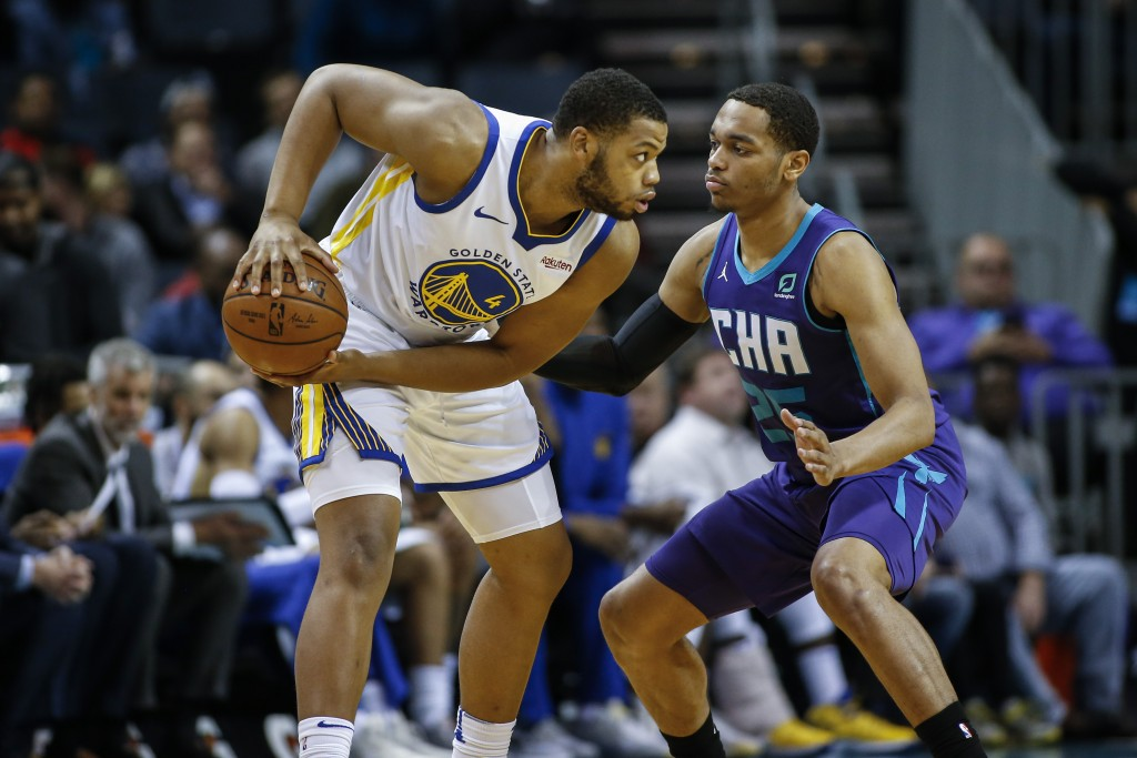 Golden State Warriors forward Omari Spellman, left, looks to pass the ball as Charlotte Hornets forward P.J. Washington defends during the first half ...