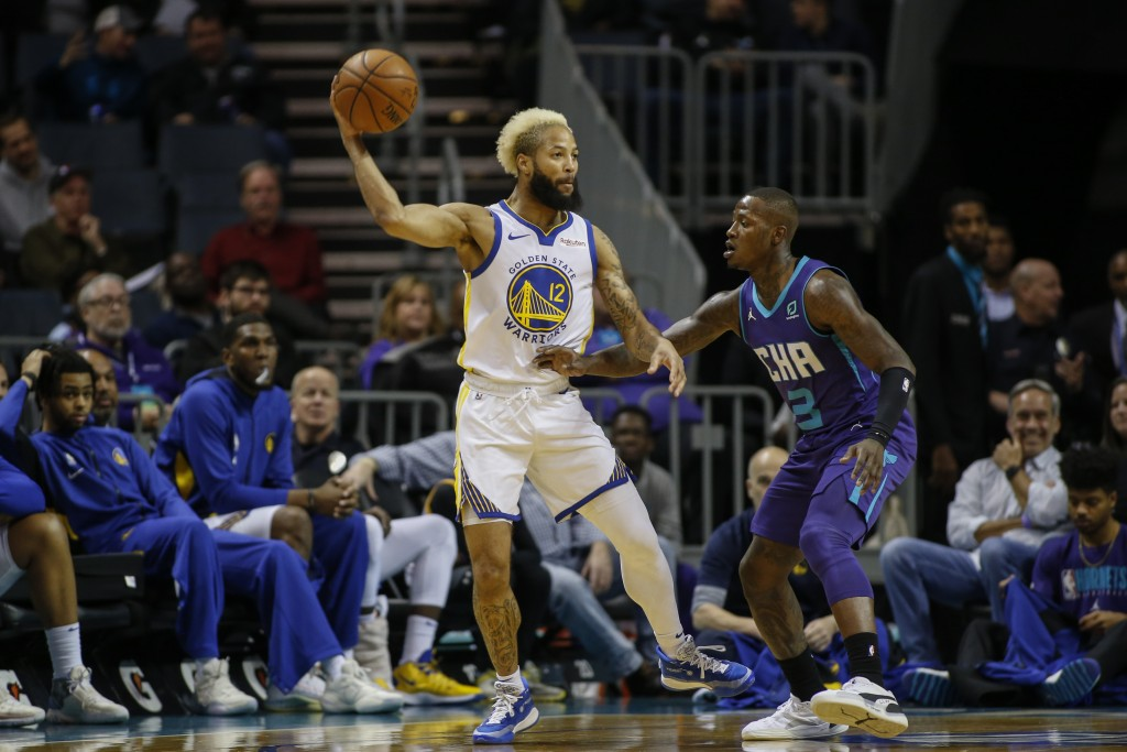 Golden State Warriors guard Ky Bowman, left, passes the ball over Charlotte Hornets guard Terry Rozier during the first half of an NBA basketball game...