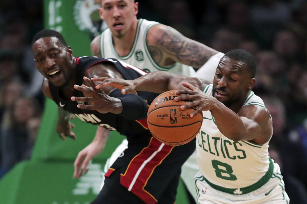 Boston Celtics guard Kemba Walker (8) steals the ball from Miami Heat center Bam Adebayo, left, during the first half of an NBA basketball game in Bos...