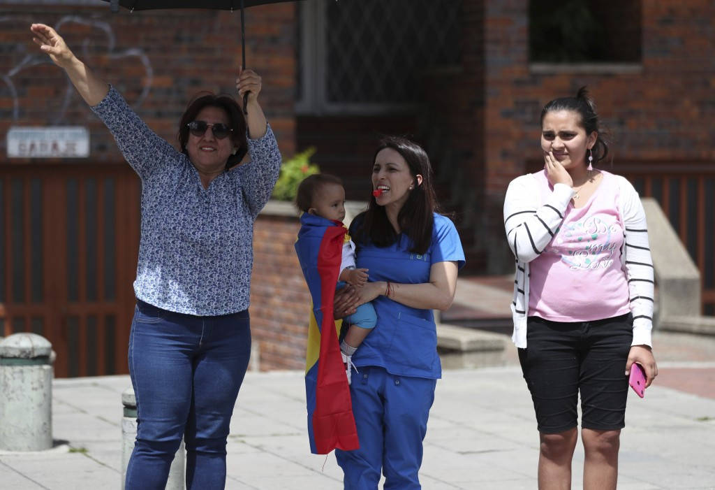 Three women show their support for an anti-government march in Bogota, Colombia, Wednesday, Dec. 4, 2019. Colombia's recent wave of demonstrations beg...