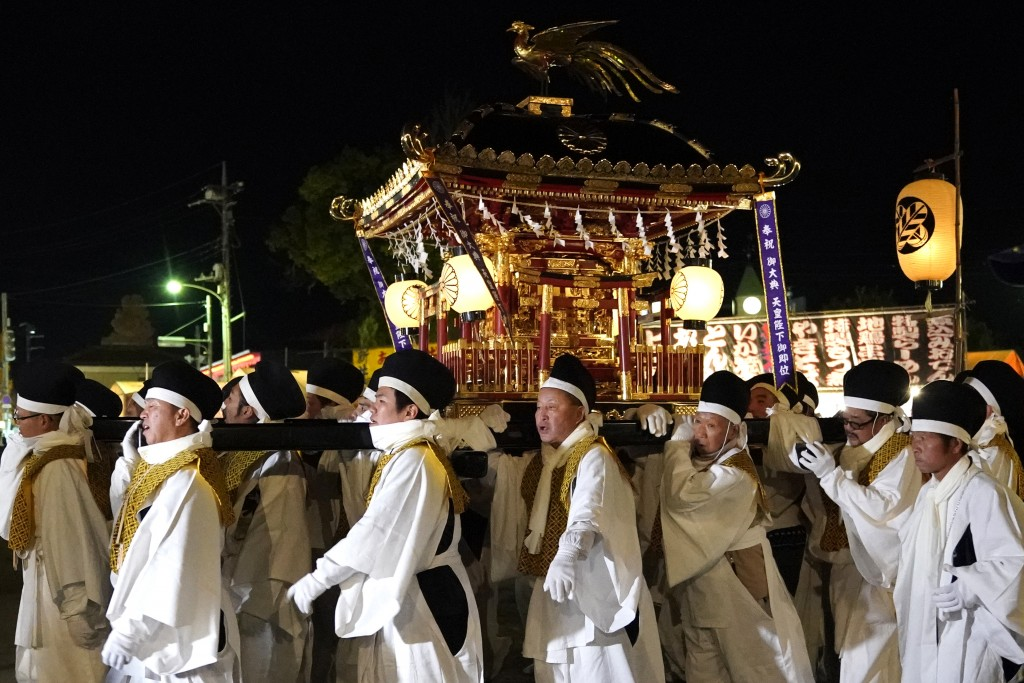In this Tuesday, Dec. 3, 2019, photo,  white-clad men carry a mikoshi, a portable shrine, during the Chichibu Night Festival in Chichibu, north of Tok...