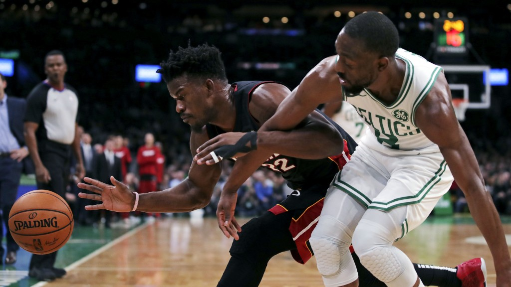 Miami Heat forward Jimmy Butler, left, battles for the loose ball against Boston Celtics guard Kemba Walker, right, during the first half of an NBA ba...