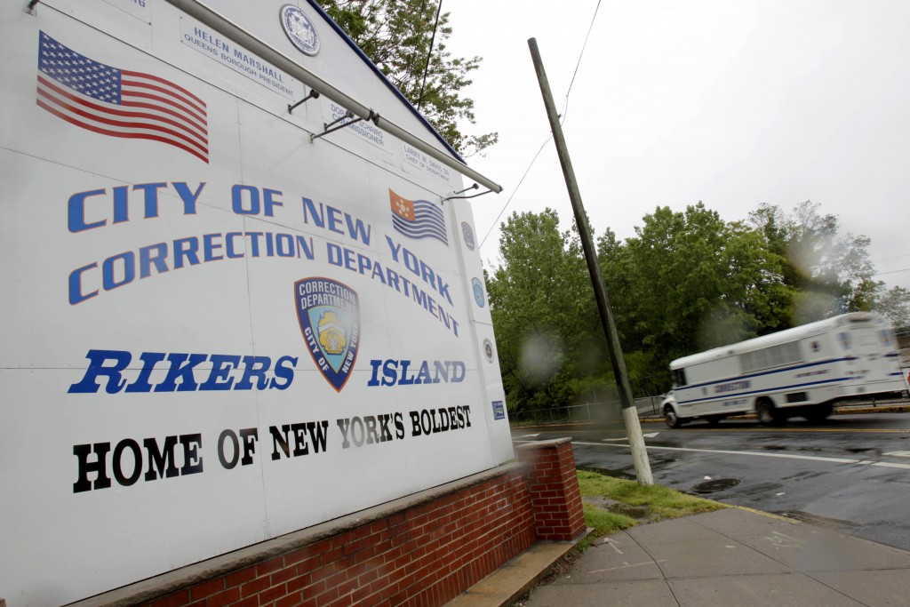 FILE - In this May 17, 2011  file photo, a New York City Department of Corrections bus passes the sign near the gate at the Rikers Island jail complex...