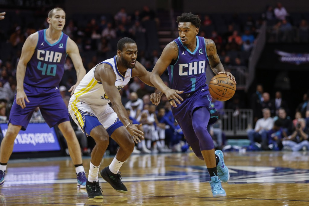 Charlotte Hornets guard Malik Monk, right, drives around Golden State Warriors guard Alec Burks during the first half of an NBA basketball game in Cha...