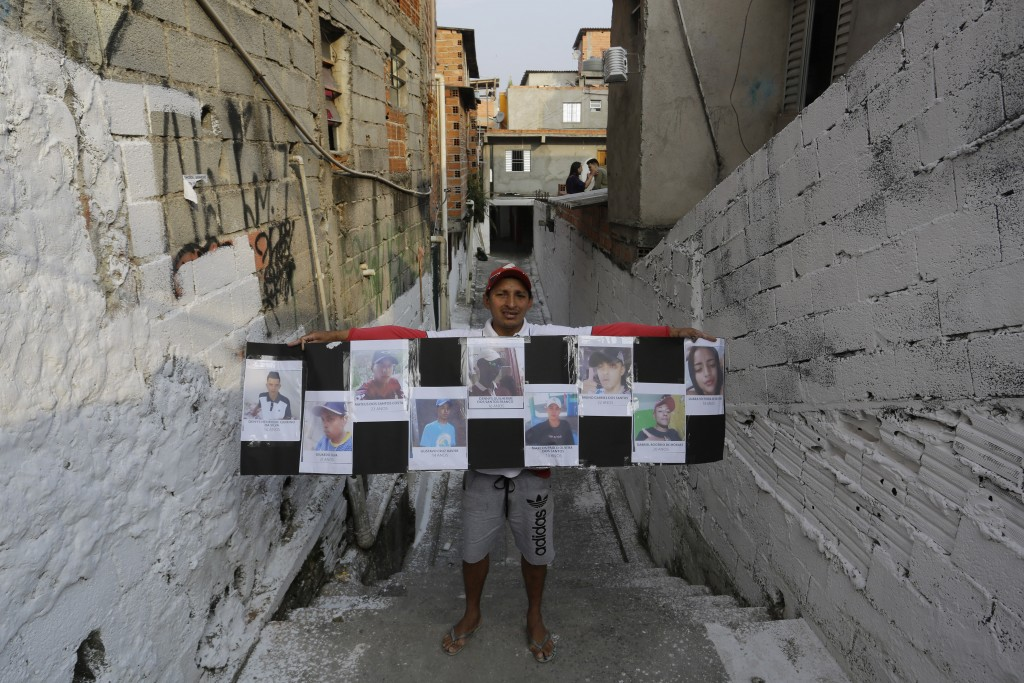 A friend holds a poster that shows images of the nine people who died in a stampede, while standing on the narrow street where they died, in Sao Paulo...
