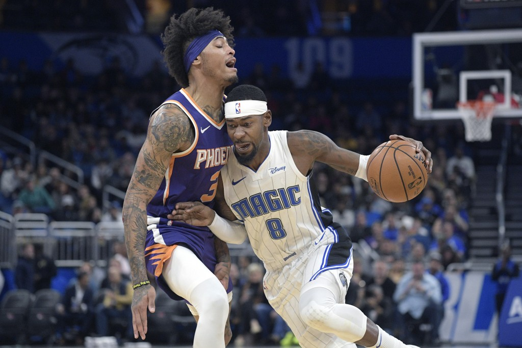 Orlando Magic guard Terrence Ross (8) drives to the basket in front of Phoenix Suns forward Kelly Oubre Jr. (3) during the first half of an NBA basket...