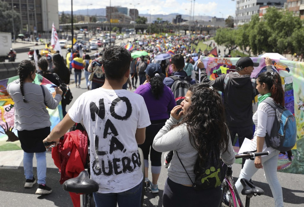 """Demonstrators, one wearing a t-shirt with text that reads in Spanish """"No to war,"""" march during a national strike in Bogota, Colombia, Wednesday, Dec. ..."""