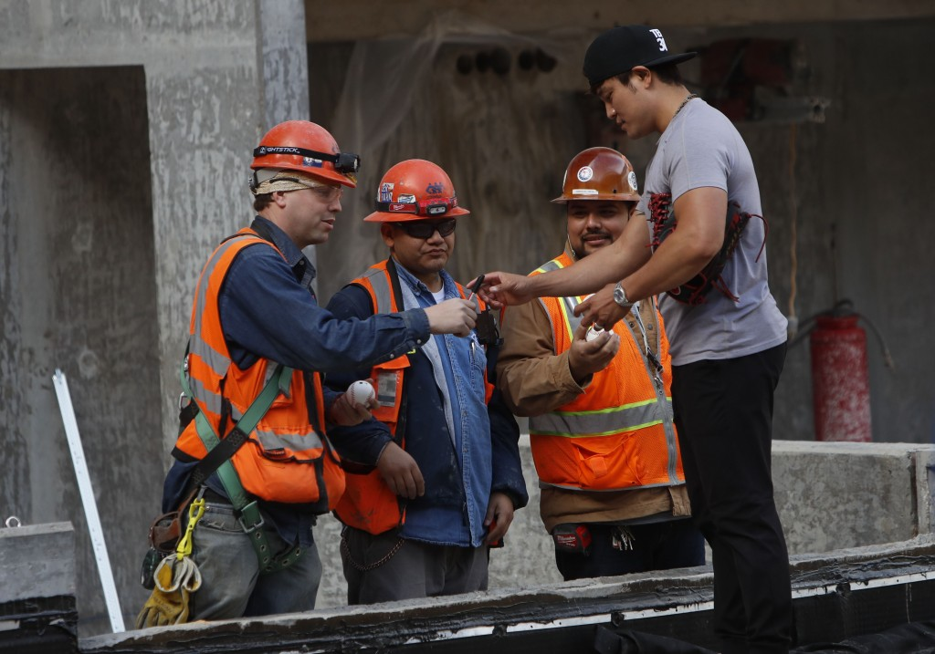 Texas Rangers outfielder Shin-Soo Choo of South Korea, right, stops to sign autographs for workers during a tour of the under construction baseball fi...