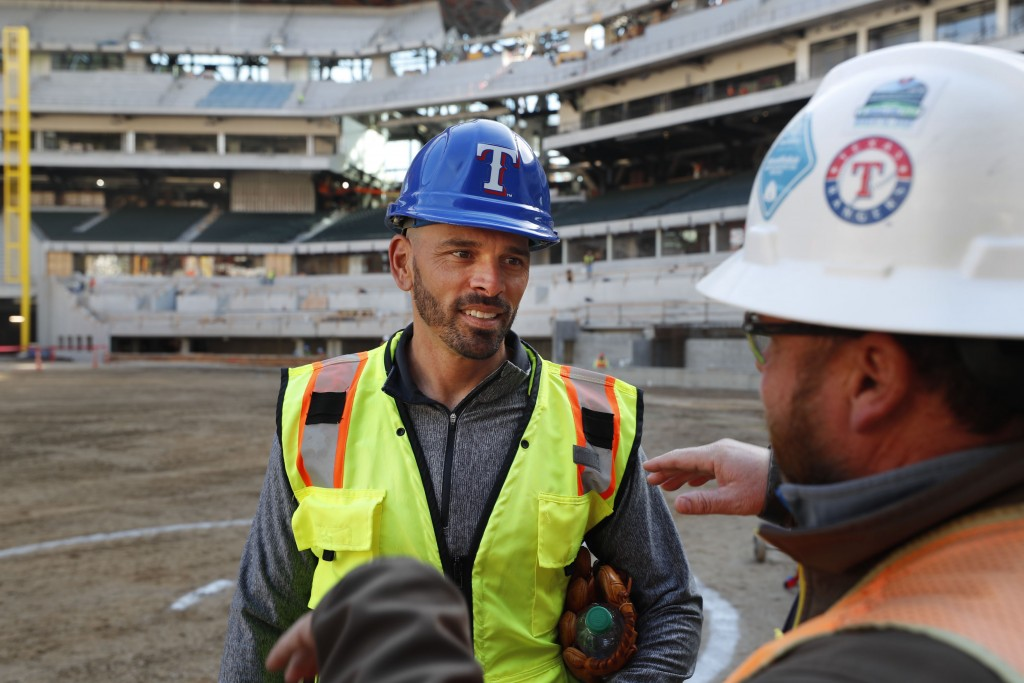 Texas Rangers manager Chris Woodward, left, listens during a tour of the under construction baseball field at the new Rangers stadium in Arlington, Te...