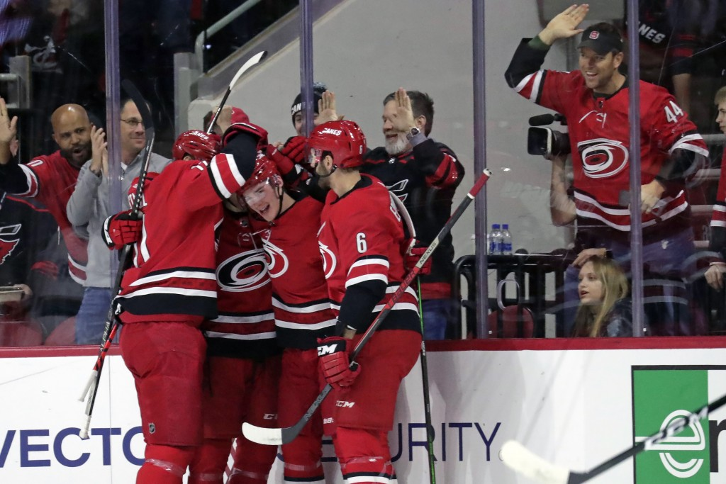 Carolina Hurricanes' Andrei Svechnikov (37) of Russia, center, celebrates his goal with Jordan Staal (11), left, and Joel Edmundson (6) during the fir...