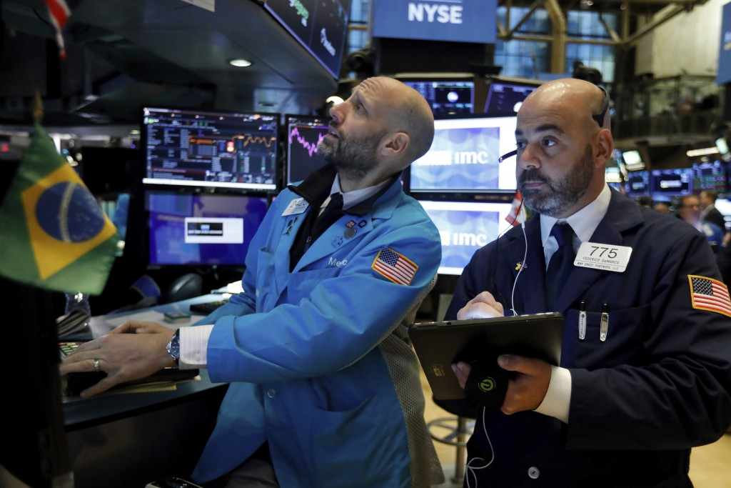 FILE - In this Nov. 15, 2019, file photo specialist Meric Greenbaum, left, and trader Fred DeMarco work on the floor of the New York Stock Exchange. T...