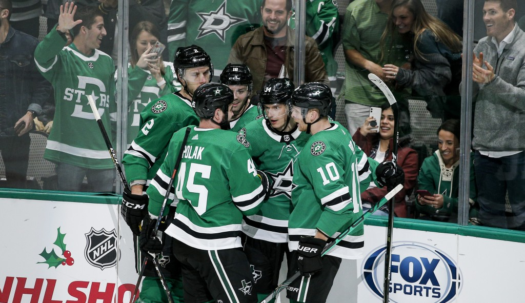 Dallas Stars forward Denis Gurianov, second from right, is congratulated by teammates after scoring a goal during the second period of an NHL hockey g...