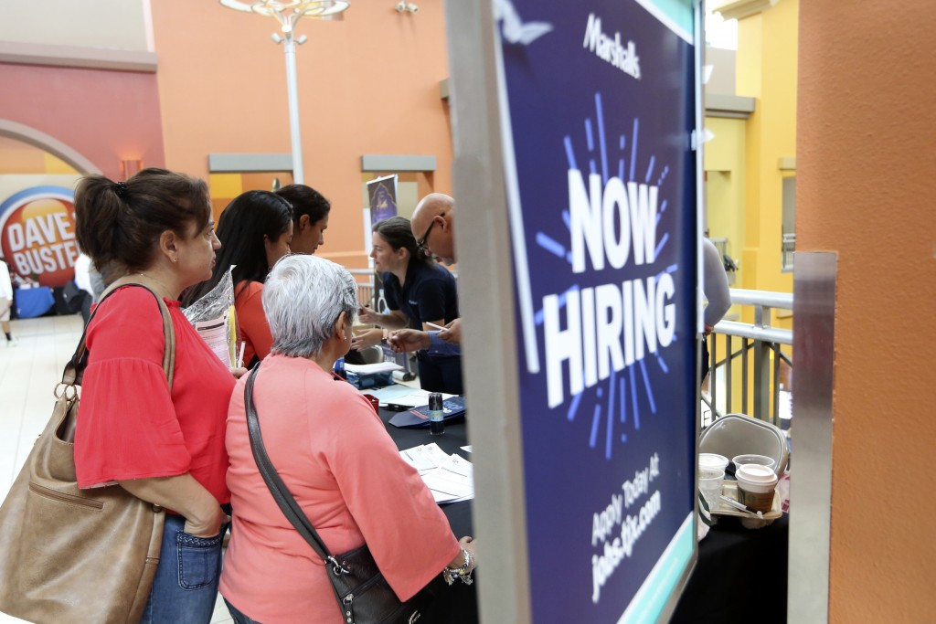 FILE - In this Oct. 1, 2019, file photo people wait in line to inquire about job openings with Marshalls during a job fair at Dolphin Mall in Miami. O...